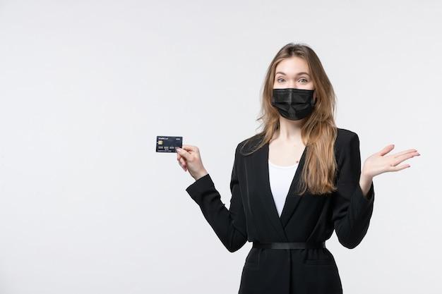 Jovem confusa empresária de terno usando sua máscara médica e segurando um cartão do banco na parede branca