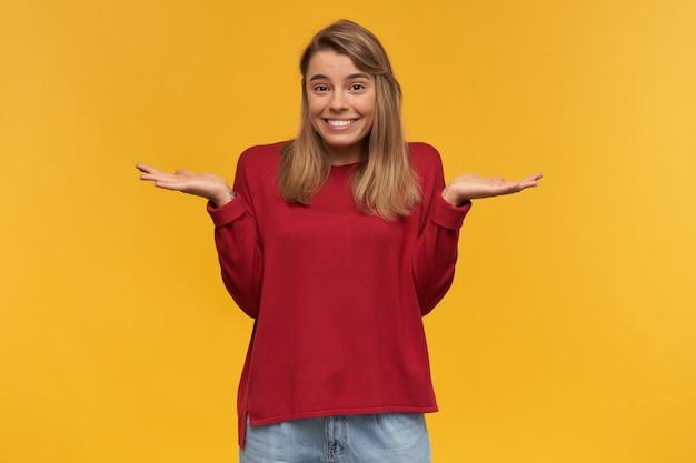 Jovem confusa, encolhendo os ombros, com olhar de culpa, sentindo pena de ter feito algo errado e cometer um erro terrível, vestida com um suéter vermelho