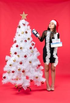 Jovem confusa linda mulher com chapéu de papai noel e em pé perto da árvore de natal decorada segurando presentes
