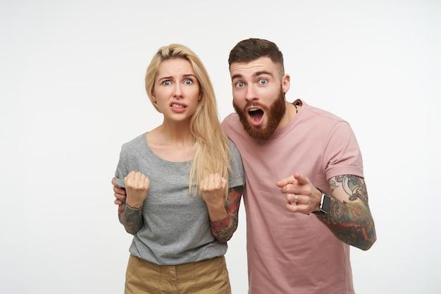 Jovem confusa loira de cabelos compridos tatuada fazendo uma careta e mantendo os punhos erguidos enquanto posava sobre um fundo branco com seu namorado barbudo moreno surpreso