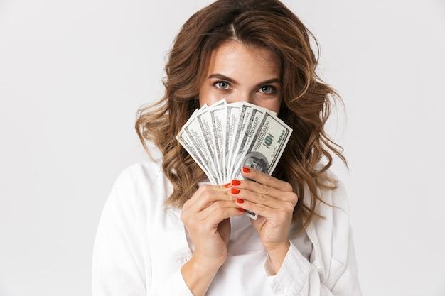 Jovem confusa segurando notas de dinheiro isoladas