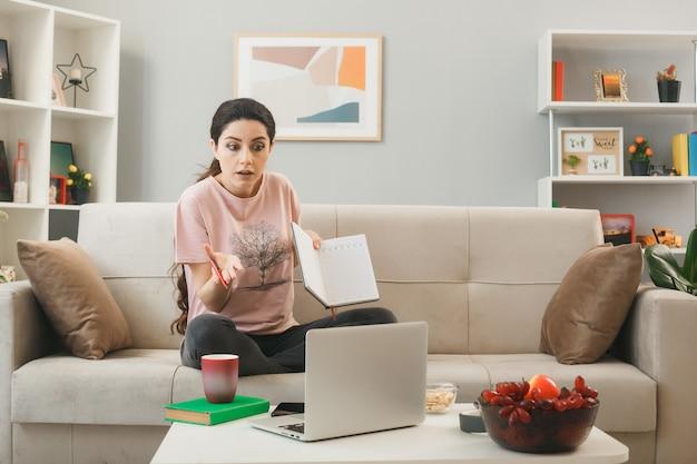 Jovem confusa segurando um caderno sentado no sofá atrás da mesa de centro, olhando para o laptop na sala de estar