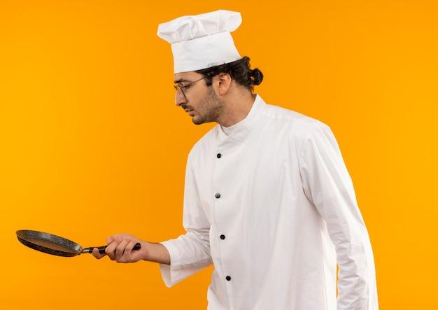 Jovem confuso cozinheiro usando uniforme de chef e óculos segurando e olhando para uma frigideira