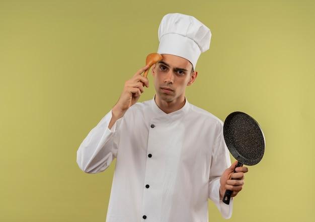 Jovem confuso cozinheiro vestindo uniforme de chef segurando a frigideira e colocando a colher na testa na parede verde isolada