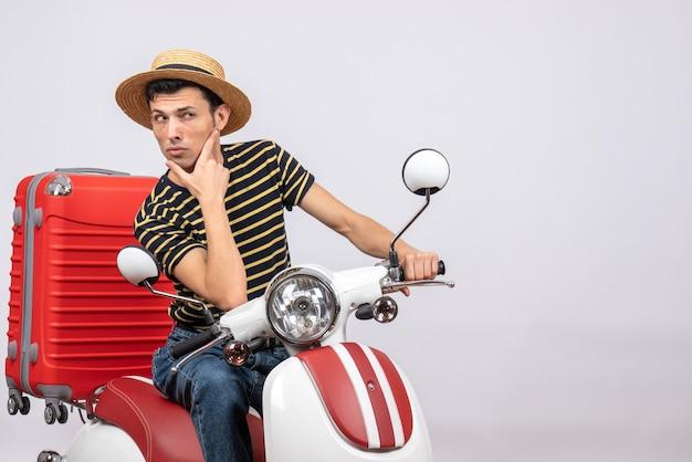 Jovem confuso de frente com chapéu de palha na motocicleta olhando para algo