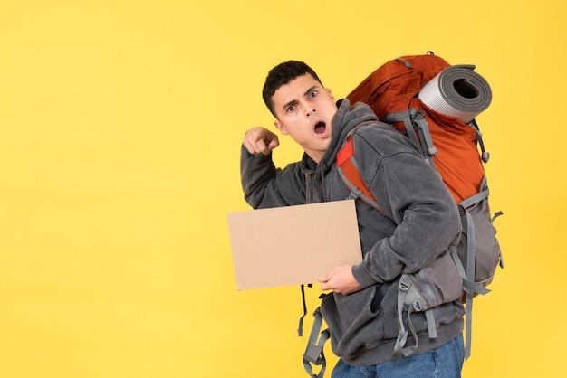 Jovem confuso de frente com uma mochila vermelha segurando um papelão