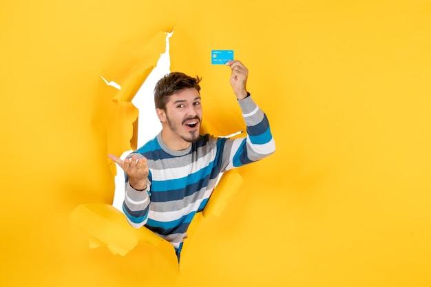 Jovem confuso de frente segurando um cartão olhando através da parede amarela de papel rasgado