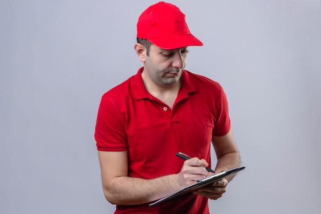 Jovem confuso entregador de camisa polo vermelha e boné segurando a área de transferência e escrevendo algo em branco com cara séria sobre parede branca isolada