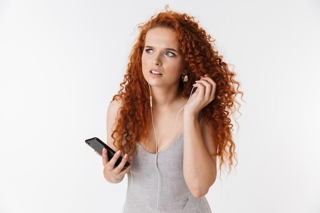 Jovem confuso incerto ruiva encaracolado mulher usando telefone celular ouvindo música.