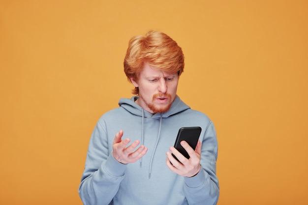 Jovem confuso ou insatisfeito com capuz falando com alguém enquanto olha para a tela do smartphone sobre a parede amarela