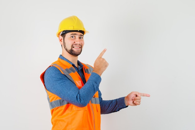 Jovem construtor apontando os dedos para cima e para o lado em camisa, colete, capacete e olhando alegre. vista frontal.