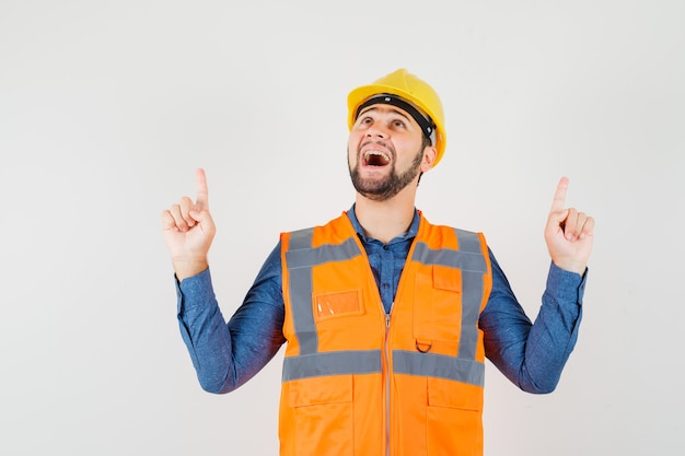 Jovem construtor apontando os dedos para cima na camisa, colete, capacete e olhando grato, vista frontal.