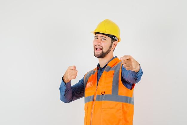 Jovem construtor apontando para a câmera na camisa, colete, capacete e parecendo confiante, vista frontal.