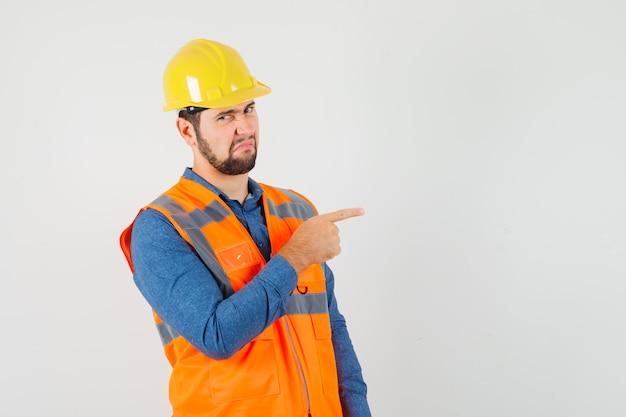 Jovem construtor apontando para o lado na camisa, colete, capacete e parecendo enojado, vista frontal.