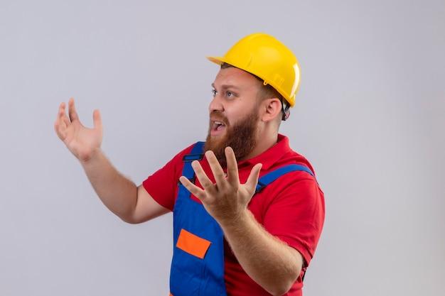 Jovem construtor barbudo chateado com uniforme de construção e capacete de segurança, encolhendo os ombros, parecendo confuso e inseguro, sem resposta, espalhando as palmas das mãos em pé sobre um fundo branco
