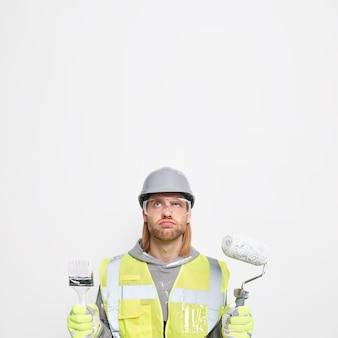 Jovem construtor barbudo e descontente segura as ferramentas de construção concentradas acima, indo pintar o teto