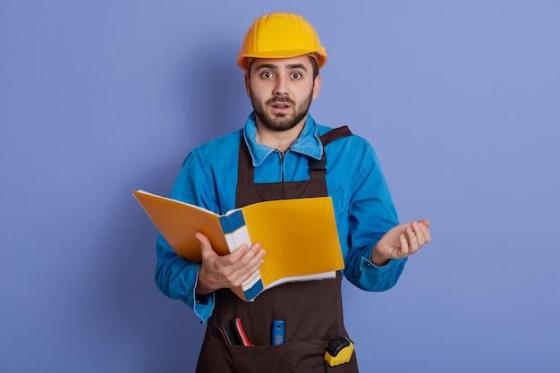 Jovem construtor chocado e espantado com capacete amarelo em pé com a boca aberta e muito surpreso