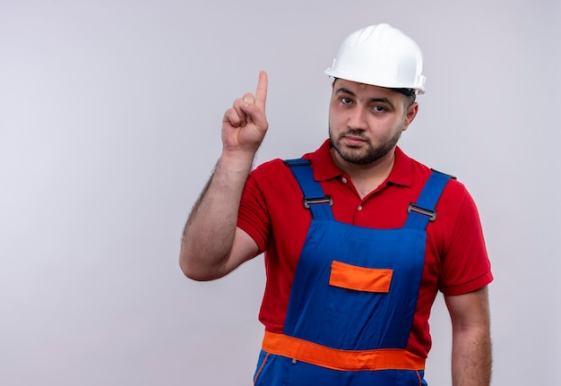 Jovem construtor com uniforme de construção e capacete de segurança apontando com o dedo indicador para cima, parecendo confiante