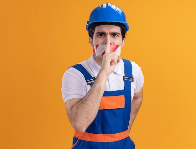 Jovem construtor com uniforme de construção e capacete de segurança com fita adesiva ao redor da boca, olhando para a frente, fazendo gesto de silêncio com o dedo nos lábios em pé sobre a parede laranja