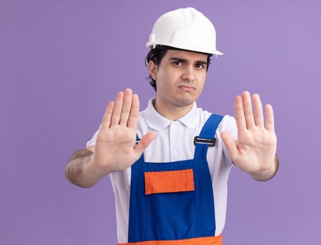 Jovem construtor com uniforme de construção e capacete de segurança na frente com rosto sério, fazendo gesto de pare com as mãos em pé sobre a parede roxa