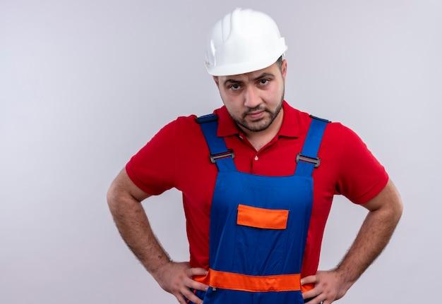 Jovem construtor com uniforme de construção e capacete de segurança, olhando para a câmera com uma cara zangada