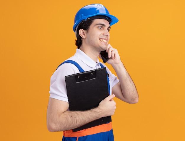 Jovem construtor com uniforme de construção e capacete de segurança segurando a prancheta, sorrindo, falando no celular, em pé sobre a parede laranja