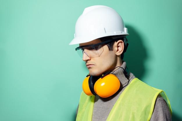 Jovem construtor confiante, engenheiro, usando fones de ouvido de segurança de construção no pescoço, capacete rígido, óculos e jaqueta reflexiva na parede de água menta.