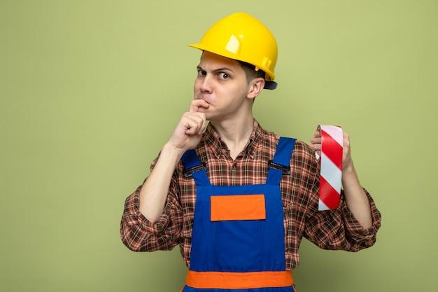 Jovem construtor do sexo masculino franzindo o cenho agarrado ao queixo usando uniforme segurando fita adesiva