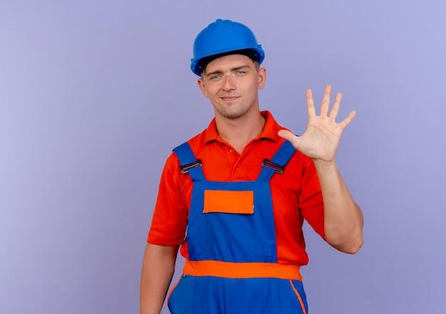 Jovem construtor do sexo masculino satisfeito usando uniforme e capacete de segurança mostrando cinco em roxo