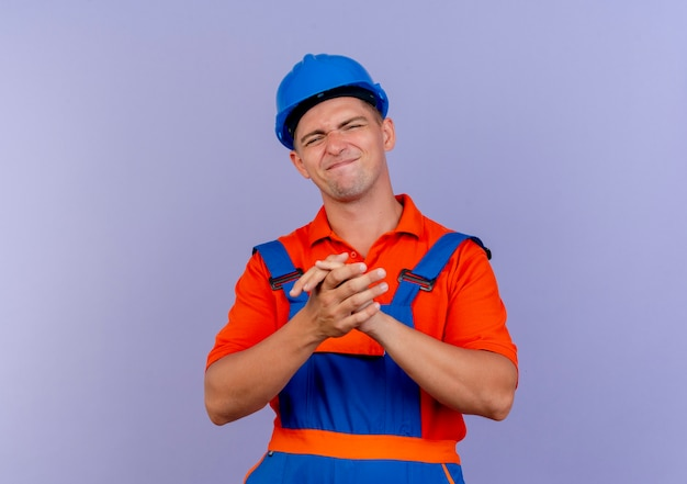 Jovem construtor do sexo masculino satisfeito usando uniforme e capacete de segurança, mostrando um gesto de aperto de mão em roxo