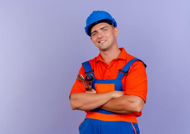 Jovem construtor do sexo masculino sorridente, usando uniforme e capacete de segurança, cruzando as mãos em roxo