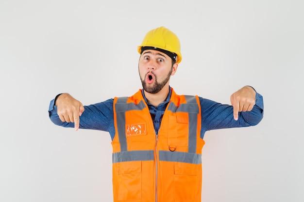 Jovem construtor em camisa, colete, capacete apontando os dedos para baixo e olhando maravilhado, vista frontal.