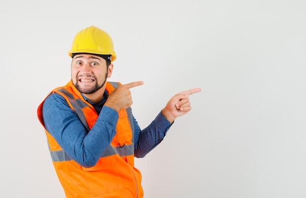 Jovem construtor em camisa, colete, capacete apontando para o lado e parecendo curioso, vista frontal.