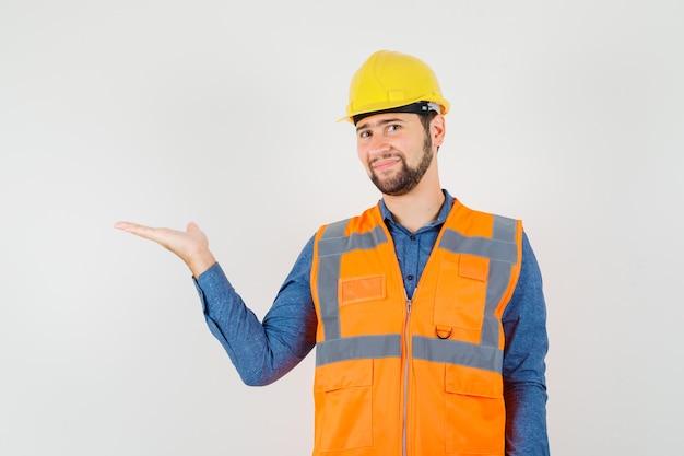 Jovem construtor em camisa, colete, capacete espalhando a palma da mão de lado e parecendo alegre, vista frontal.