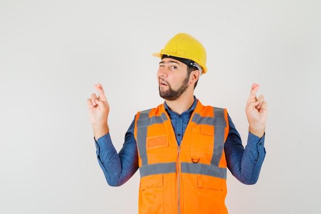 Jovem construtor em camisa, colete, capacete mantendo os dedos cruzados e o olho piscando, vista frontal.