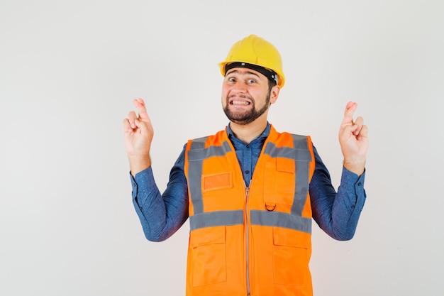 Jovem construtor em camisa, colete, capacete, mantendo os dedos cruzados e parecendo feliz, vista frontal.