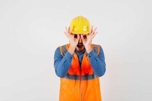 Jovem construtor em camisa, colete, capacete, mostrando gesto de óculos e olhando engraçado, vista frontal.
