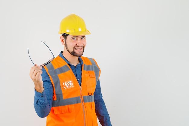 Jovem construtor em camisa, colete, capacete segurando óculos e olhando alegre, vista frontal.