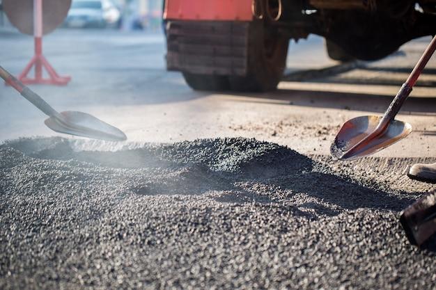 Jovem construtor em máquina pavimentadora de asfaltagem durante obras de reparação de estradas