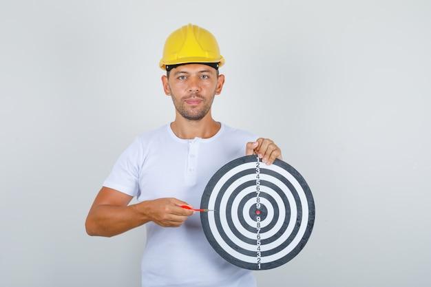 Jovem construtor em t-shirt branca, capacete de segurança segurando o alvo de dardos e a flecha de dardo, vista frontal.