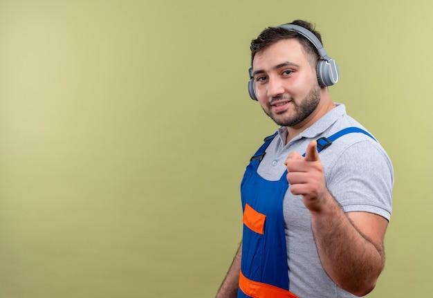 Jovem construtor em uniforme de construção com fones de ouvido sorrindo com uma cara feliz apontando com o dedo indicador para a câmera