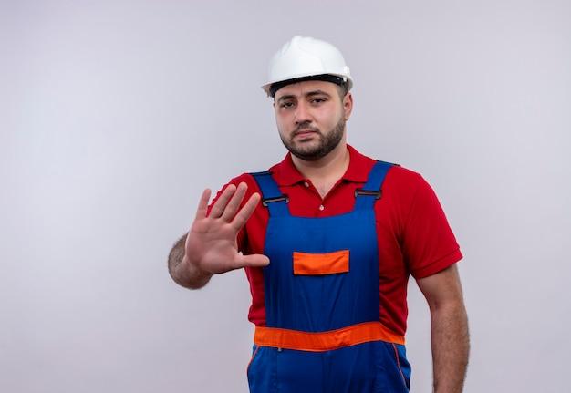 Jovem construtor em uniforme de construção e capacete de segurança com a mão aberta, fazendo sinal de pare com uma cara séria