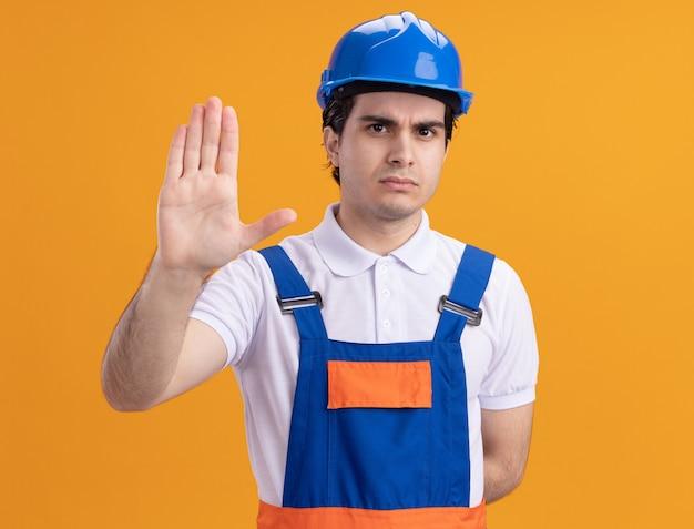 Jovem construtor em uniforme de construção e capacete de segurança olhando para frente com uma cara séria, fazendo gesto de parada com a mão em pé sobre a parede laranja