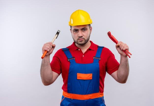 Jovem construtor em uniforme de construção e capacete de segurança segurando chaves nos braços erguidos, olhando para a câmera com cara de raiva