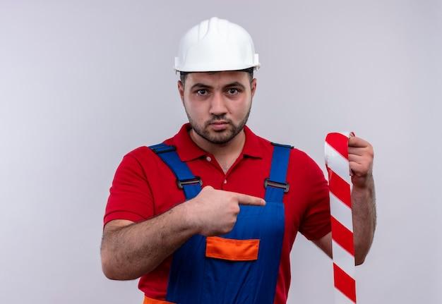 Jovem construtor em uniforme de construção e capacete de segurança segurando fita adesiva apontando com o dedo indicador para ela com uma expressão séria