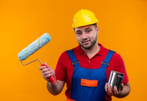 Jovem construtor em uniforme de construção e capacete de segurança segurando rolo de pintura e lata de tinta sorrindo