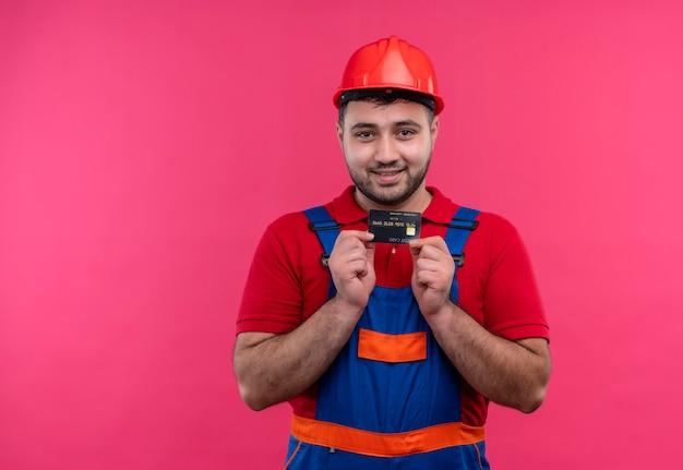 Jovem construtor em uniforme de construção e capacete de segurança segurando um cartão de crédito, sorrindo com uma cara feliz