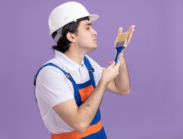 Jovem construtor em uniforme de construção e capacete de segurança segurando um pincel e olhando para ele com amor em pé sobre a parede roxa