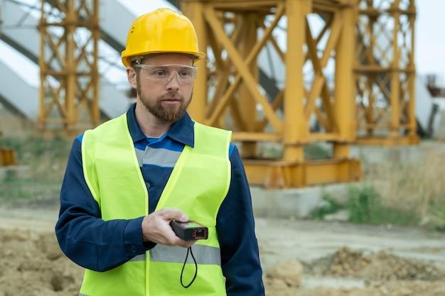 Jovem construtor em uniforme e capacete de proteção e óculos usando ferramenta de trabalho