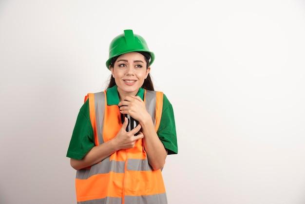 Jovem construtor feminino segurando a taça preta. foto de alta qualidade